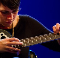 Kaki King taps the neck of her guitar.